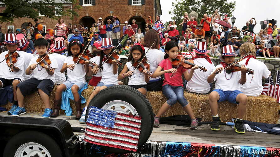Violinists play patriotic songs during the Independence Day parade in Fairfax, Virginia, July 4, 2015.