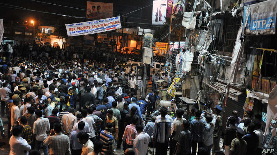 Indian authorities and onlookers are pictured at the site of a bomb blast at Dilshuk Nagar in Hyderabad on February 21, 2013.