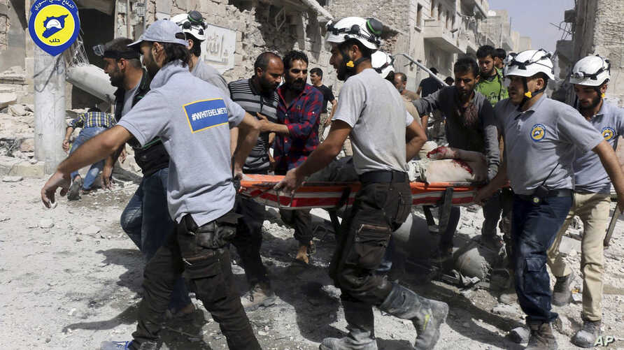FILE - White Helmets rescue workers work the site of airstrikes in the al-Sakhour neighborhood of the rebel-held part of eastern Aleppo, Syria, Sept. 21, 2016.