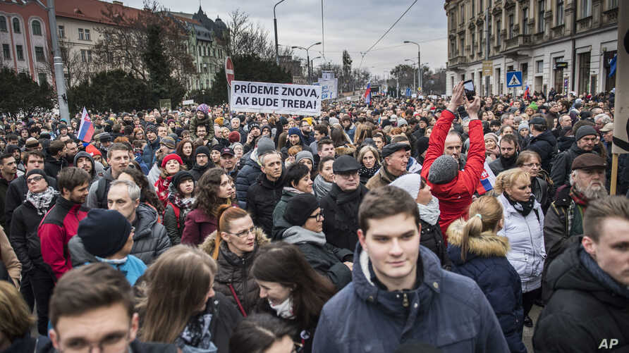 "Protesters hold a banner reading ""I do care about it"" during a mass quiet march in Bratislava, Slovakia, March 23, 2018.  Many thousands of Slovaks took to the streets in anti-government protests amid a continuing political crisis triggered by the re"
