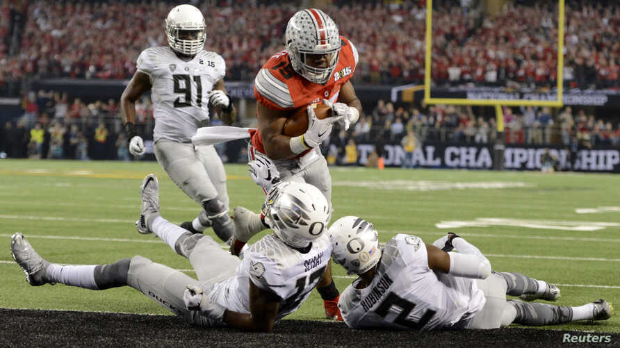 Ohio State Buckeyes running back Ezekiel Elliott (15) runs for a touchdown against Oregon Ducks defensive back Tyree Robinson (2) and defensive back Chris Seisay (12) during the third quarter in the 2015 CFP National Championship Game, Jan. 12, 2015.