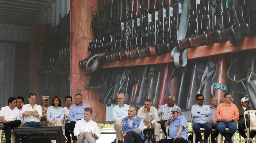 Colombia's President Juan Manuel Santos, front left, top commander of the Revolutionary Armed Forces of Colombia, FARC, Rodrigo Londono, also known as Timoleón Jiménez or Timochenko, front right, and Jean Arnault, U.N. representative for the Colomb...