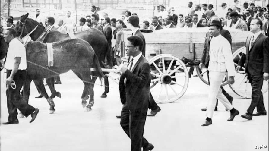 FILE - (FILES) Two mules pull a cart carrying the coffin of the US clergyman, leader of the Movement against Racial Segregation and Nobel Peace Prize winner Martin Luther King during his funeral, 9 April 1968, in Atlanta.