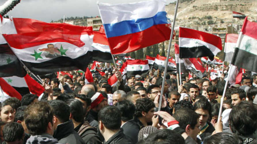 Supporters of Syria's President Bashar al-Assad hold up national flags and a Russian flag as they attend a rally at Umayyad square in Damascus, Syria, March 15, 2012.