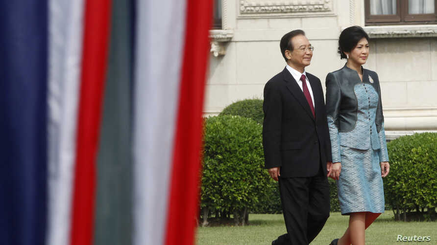 Chinese Premier Wen Jiabao (L) walks with Thai Prime Minister Yingluck Shinawatra during a welcoming ceremony at the Government House in Bangkok, November 21, 2012.