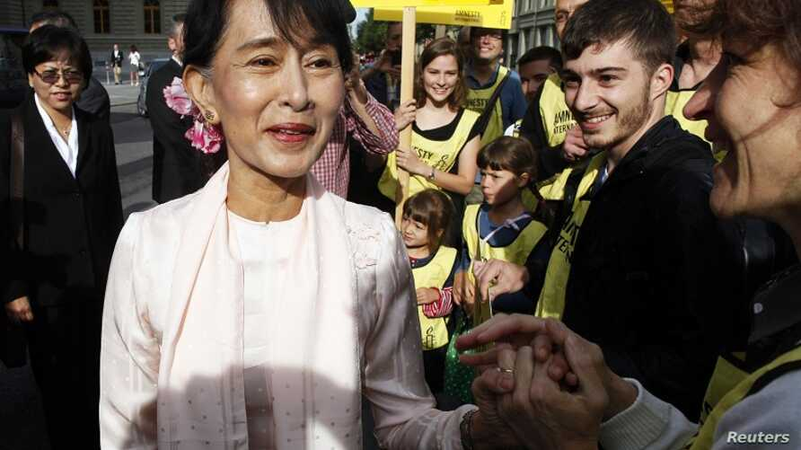 Burma's opposition leader Aung San Suu Kyi is welcomed by supporters outside the Swiss Parliament building in Bern June 15, 2012.