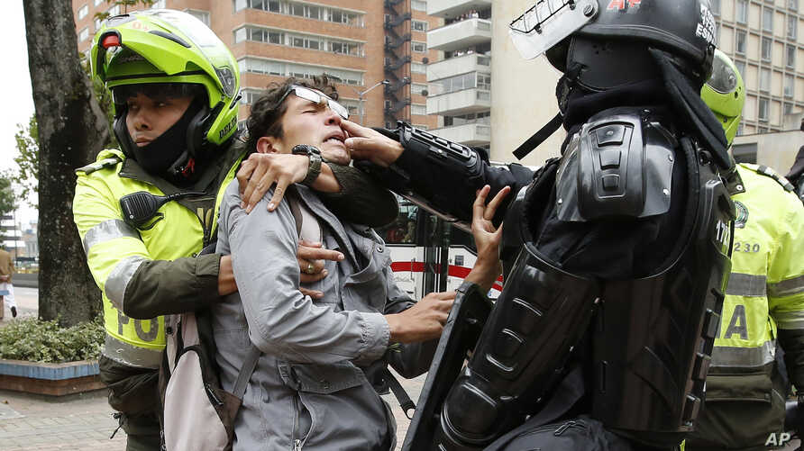 FILE - Police detain a man who was blocking traffic during a protest against a decree by Colombia's President Ivan Duque that would allow police to confiscate any amount of drugs from people in the street in Bogota, Colombia, Sept. 6, 2018.