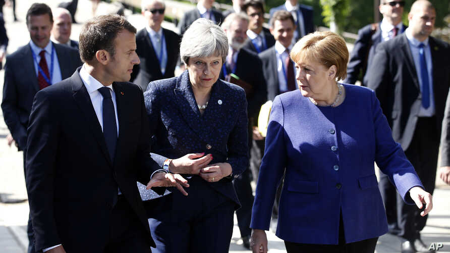 German Chancellor Angela Merkel, right, speaks with French President Emmanuel Macron, left, and British Prime Minister Theresa May after meeting at a hotel on the sidelines of an EU-Western Balkans summit in Sofia, Bulgaria, May 17, 2018.