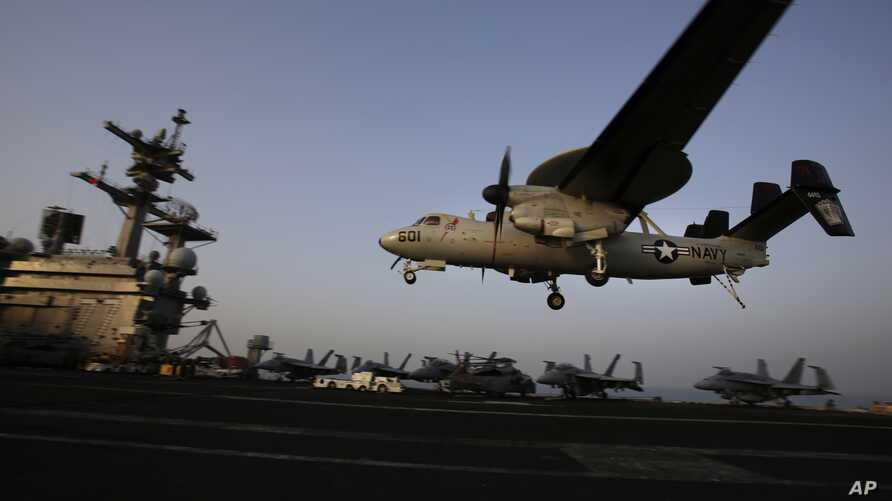FILE - An aircraft lands after missions targeting the Islamic State group in Iraq from the deck of the U.S. Navy aircraft carrier USS George H.W. Bush in the Persian Gulf, Aug. 10, 2014.