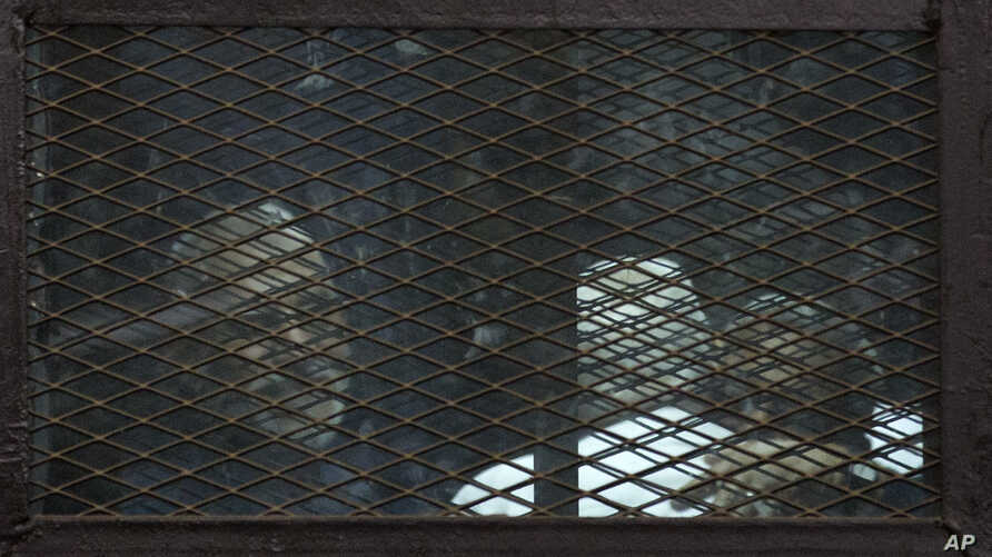 FILE - Members of Egypt's now banned Muslim Brotherhood are seen in detention in Cairo.