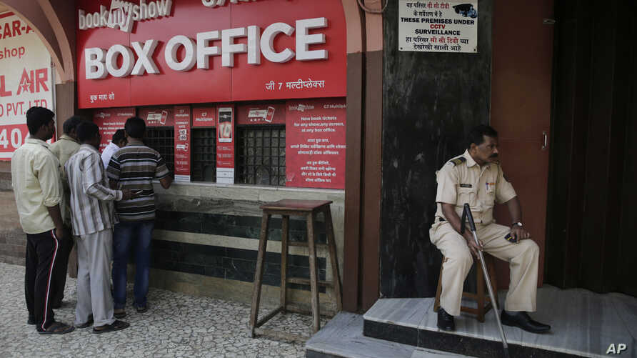 """A policeman guards as people buy tickets at a movie theatre screening Bollywood film """"Padmaavat"""" in Mumbai, India, Jan. 25, 2018."""