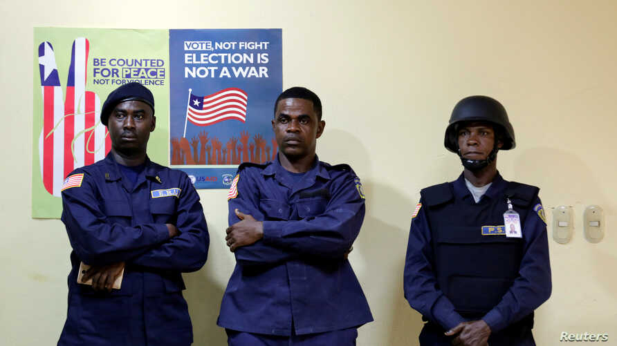 FILE - Police officers stand guard at National Election Commission headquarters in Monrovia, Liberia, Oct. 11, 2017.