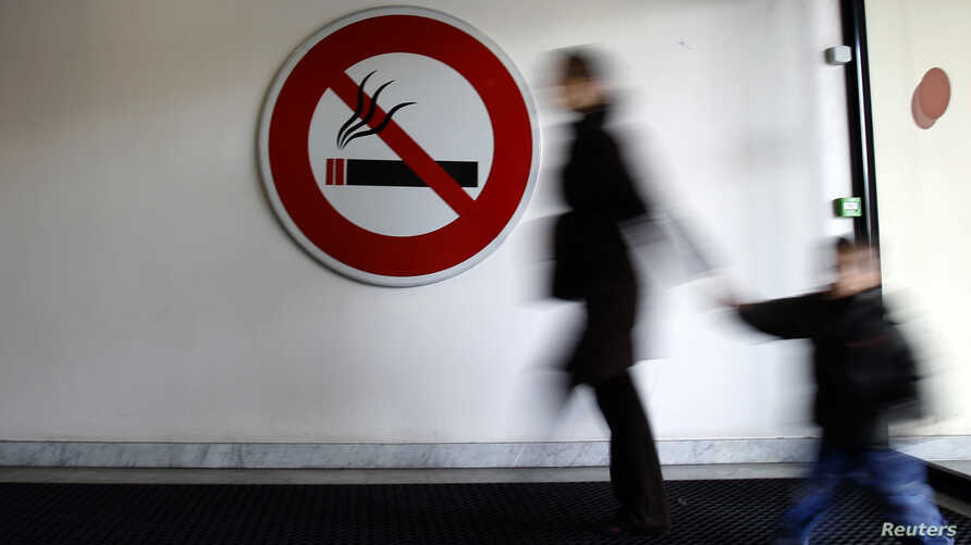 """A woman walks past a """"No Smoking"""" sign in Nice"""