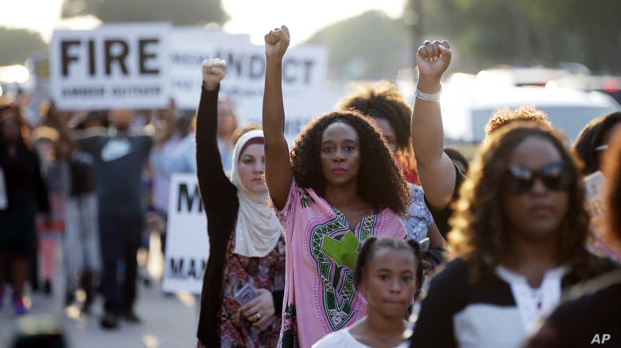 FILE - Demonstrators march in Arlington, Texas, Sept. 16, 2018, to protest the recent killings of two black men by police: Botham Jean and O'Shae Terry. On Friday, Amber Guyger, a former police officer, was charged with murder in the shooting death o