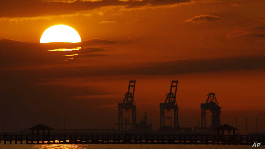 FILE- In this Dec. 2, 2018, file photo cranes at the Port of Gulfport are silhouetted by the setting sun at Gulfport, Mississippi.