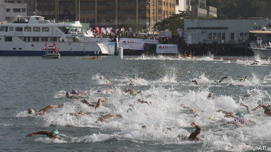 FILE - Competitors swim during the annual 1.5-kilometer (0.93-mile) harbor race at the Victoria Harbor in Hong Kong, Oct. 18, 2015.