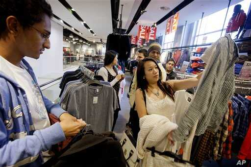 In this Wednesday, Dec. 12, 2012, photo, Lana Nguyen, right, holds up a shirt while helping friend Chris Ghiathi, left, shop in an H&M store, in Atlanta.