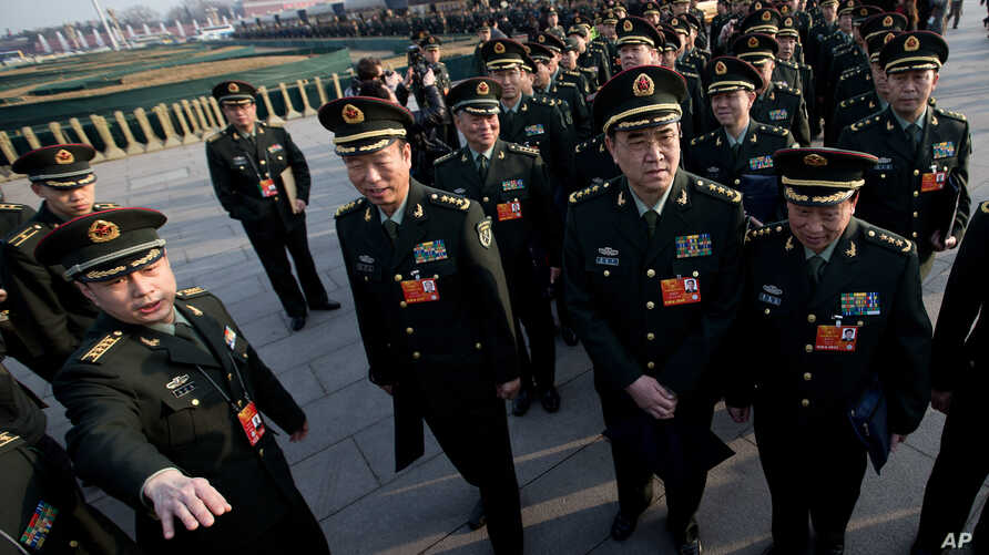 Delegates from Chinese People's Liberation Army line up on Tiananmen Square as they prepare to walk toward the Great Hall of the People for the opening session of the National People's Congress, March 5, 2013.
