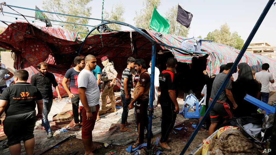 People gather at the site of a suicide bomb attack in al-Shaab district, Baghdad, Iraq, Oct.15, 2016.