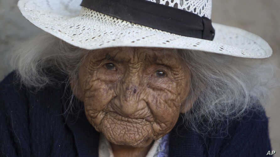 FILE - Julia Flores Colque, 117 years old, sits outside her home in Sacaba, Bolivia, Aug. 23, 2018.