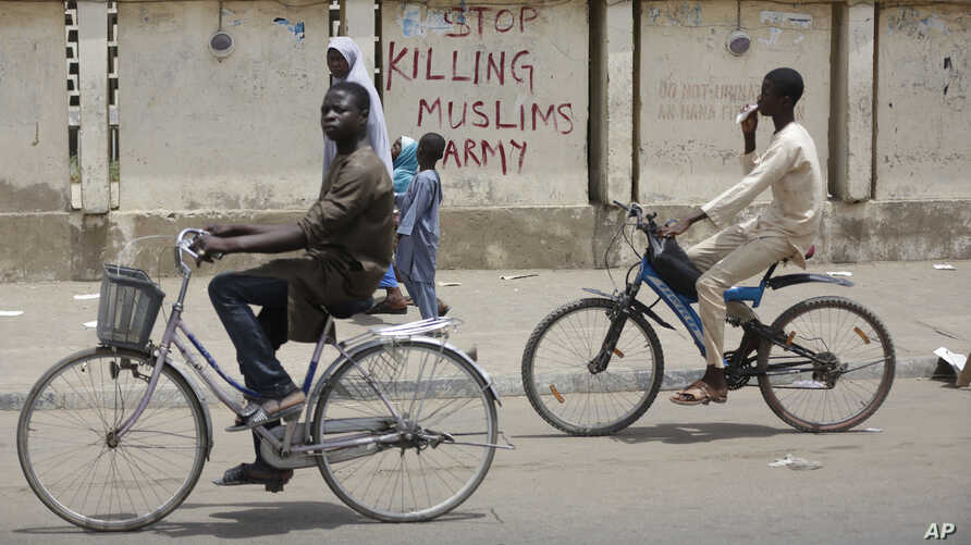 """Two boys ride their bicycles past a sign reading """"Stop killing Muslims Army"""" on a wall in Kano, Nigeria, April 8, 2016. Nigeria's Kaduna state government has secretly buried hundreds of minority Shi'ite Muslims in a mass grave."""