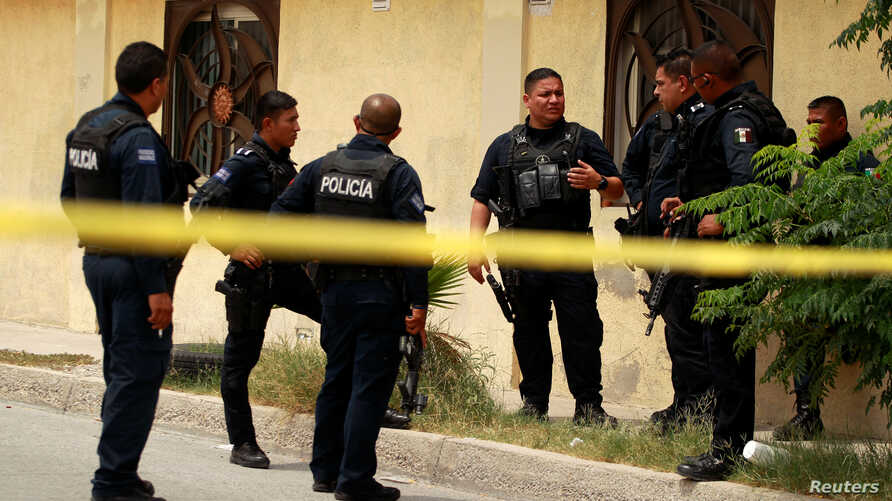 Police officers guard a crime scene where the bodies of several people were found inside a house, days before the visit of Mexico's President-Elect Andres Manuel Lopez Obrador, in Ciudad Juarez, Aug. 3, 2018.