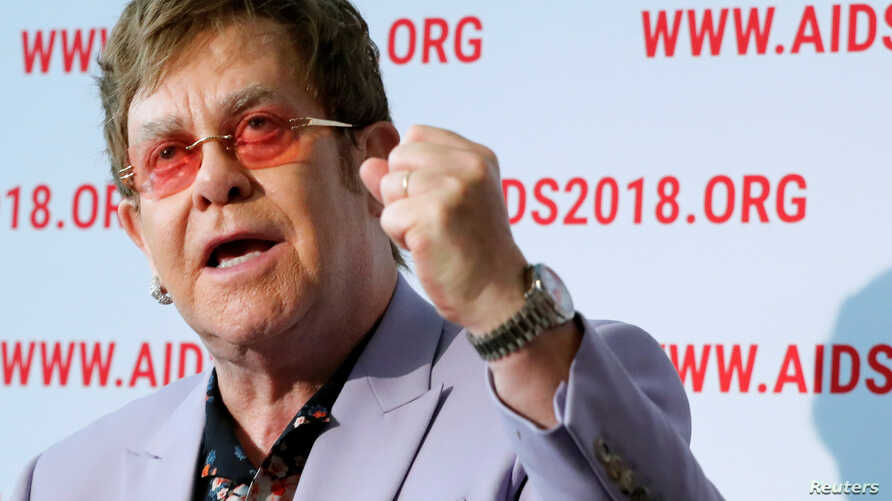 British musician Elton John raises his fist as he delivers a news conference at the 22nd International AIDS Conference (AIDS 2018), the largest HIV/AIDS-focused meeting in the world, in Amsterdam, Netherlands, July 24, 2018.