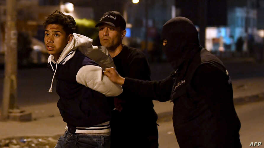 FILE - Tunisian security forces detain a protester on the outskirts of Tunis, Jan. 10, 2018.