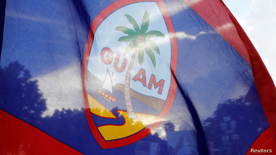 FILE - Local residents display a Guam flag during a peace rally at Chief Quipuha Park, on the island of Guam, a U.S. Pacific Territory, Aug. 14, 2017. Guam wants to decide its future with a nonbinding vote.