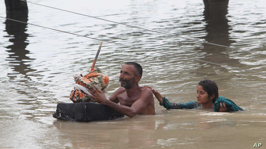 Pakistan villagers wade through floodwaters in Rajanpur, Pakistan, Thursday, July 23, 2015.