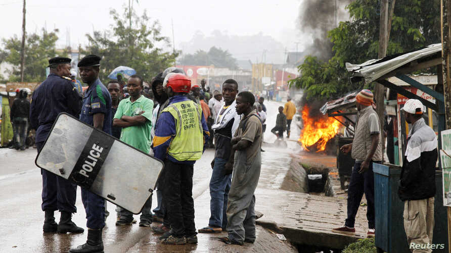 Residents block a road as they protest the killings of two locals, in Beni in North Kivu province, Democratic Republic of Congo, Oct. 22, 2014.