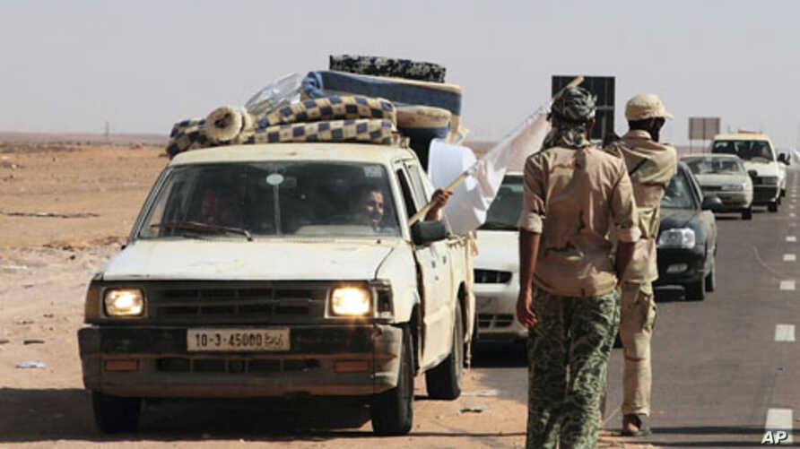 A man waves a white flag from a car loaded with his family and their belongings at a rebel checkpoint 99 miles (160 kilometers) from Sirte, Libya, August 28, 2011