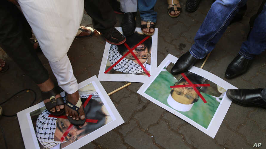 Indian protesters stamp placards with pictures of Pakistani Mujahiddeen leader Masood Azhar, left and Jama'at-ud-Da'wah chief Hafiz Muhammad Saeed, right, as they condemn the attack on the Pathankot air force base in Mumbai, India, Jan.4, 2016.