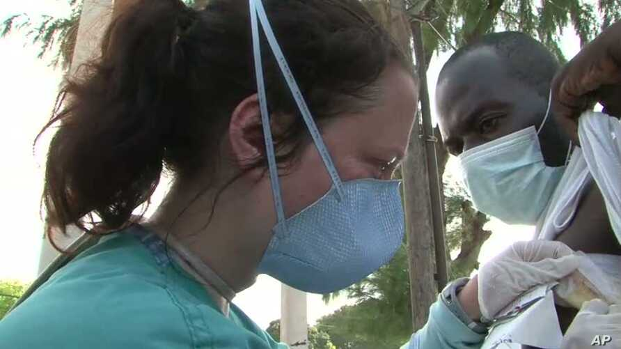 Dr. Megan Coffee examines a patient named Stanley who has tuberculosis at Port-au-Prince Hospital