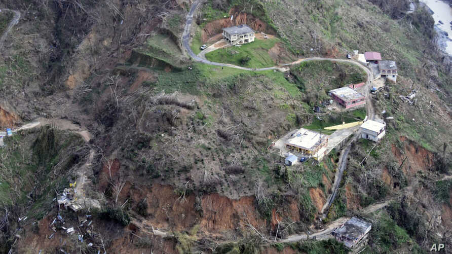 This photo made available by the U.S. Coast Guard, shows homes near a washed out road in Utuado, Puerto Rico, Oct. 3, 2017.