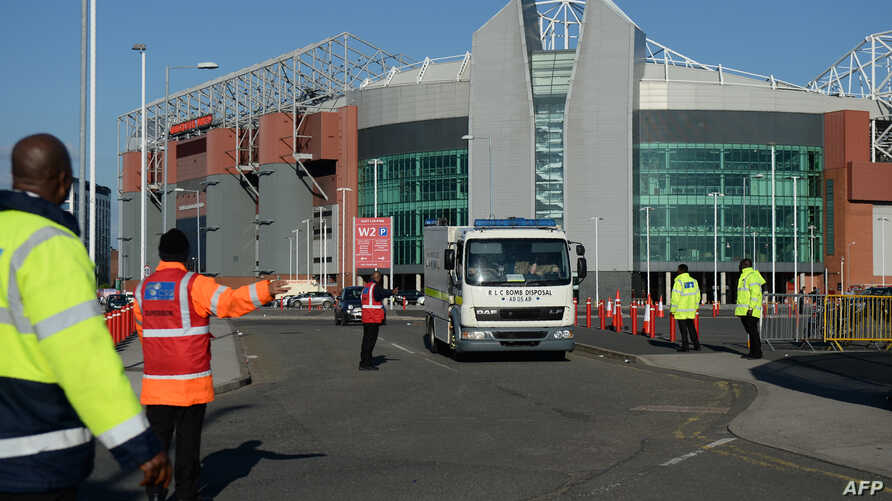 Event staff guide a British Army Bomb Disposal Unit truck as it leaves Old Trafford stadium in Manchester, north west England, on May 15, 2016, after the English Premier League football match between Manchester United and Bournemouth was canceled..