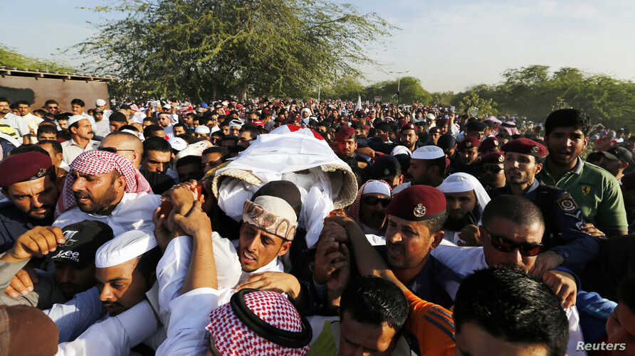FILE -  Mourners carry the body of one of the three policemen who were killed, March 3, 2015, by a remotely detonated bomb in the village of Daih. Two Bahrainis and one Emirati  made up the three dead officers.