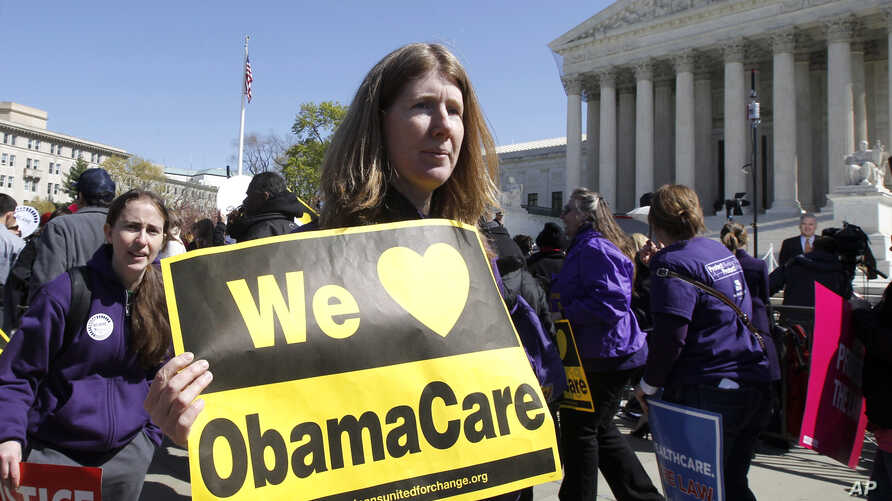 Holding a sign saying 'We Love ObamaCare' supporters of health care reform rally in front of the Supreme Court in Washington, March 27, 2012.
