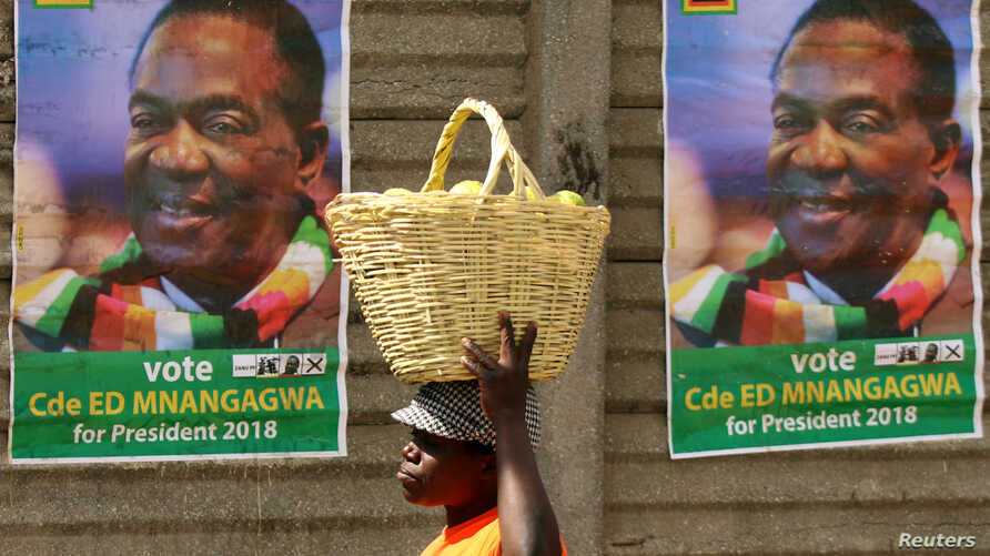FILE - A street vendor carries fruit outside an election rally of President Emmerson Mnangagwa's ruling ZANU-PF party in Mutare, Zimbabwe, May 19, 2018.