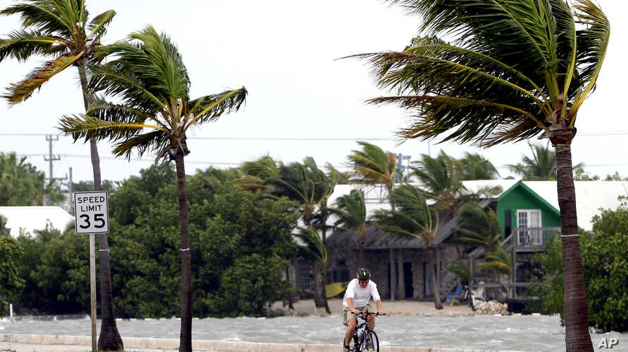 A cyclist rides his bike in Key West, Florida, Sunday, Aug. 26, 2012. Tropical Storm Isaac gained fresh muscle Sunday as it bore down on the Florida Keys, with forecasters warning it could grow into a dangerous Category 2 hurricane as it nears the no