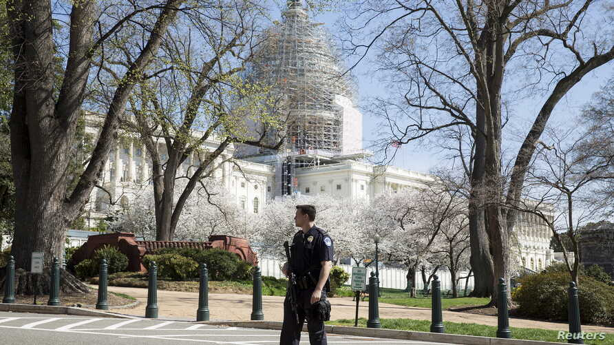 Police guard the U.S. Capitol grounds after a shooting took place, in Washington April 11, 2015.