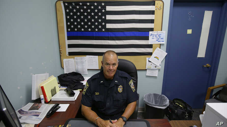 FILE - Taunton police Lt. Paul Roderick sits behind his desk at police headquarters in Taunton, Mass., July 11, 2017.