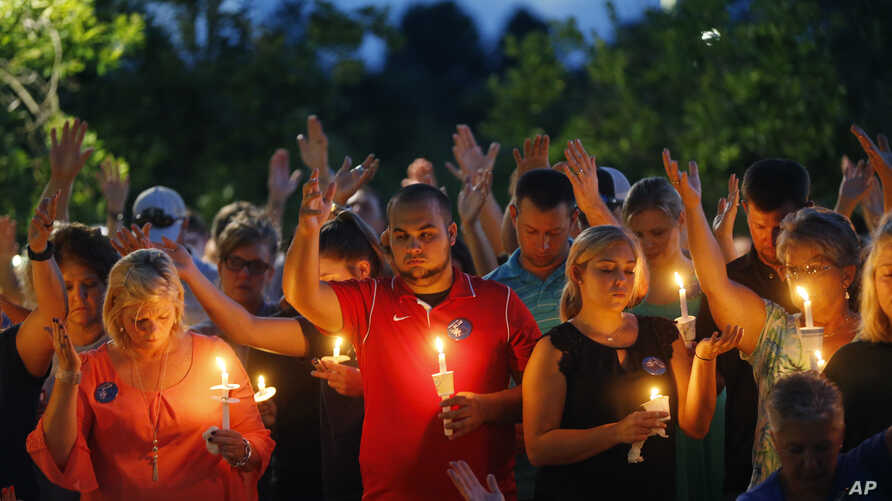People hold up their hands in prayer during a candlelight vigil for fallen Baton Rouge police officers at the Healing Place Church in Baton Rouge, Monday, July 18, 2016.
