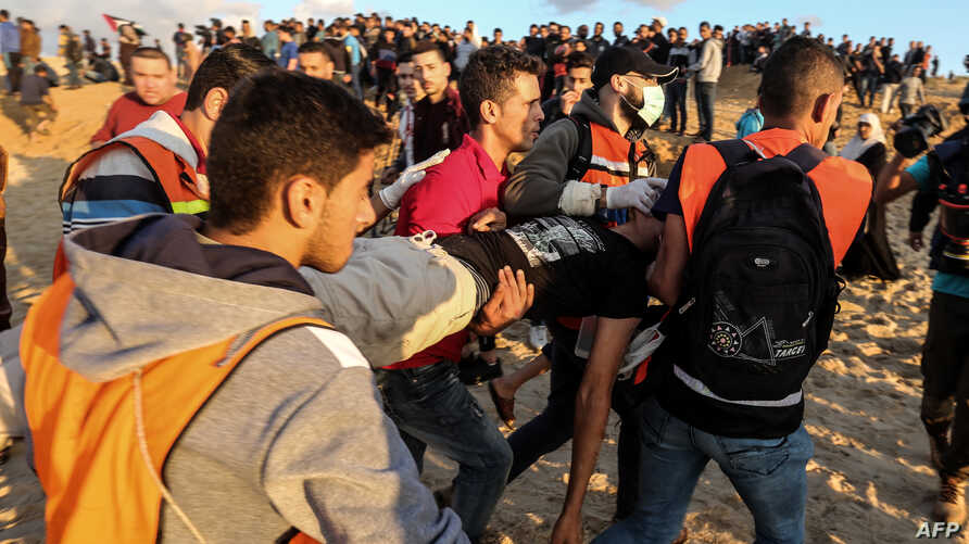 Palestinians carry away a protester during a demonstration calling for an end to the Israeli blockade on Gaza, on a beach in Beit Lahia near the maritime border with Israel, Nov. 5, 2018.