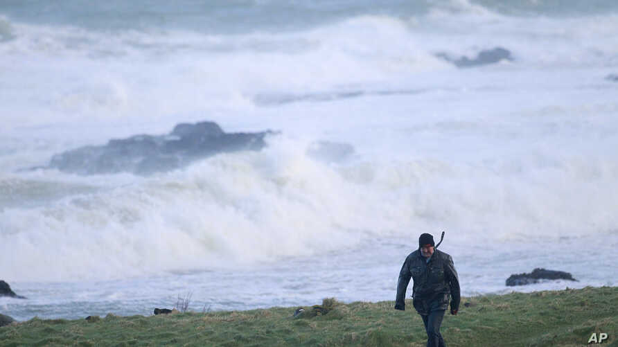 FILE - A man struggles in the strong winds in Portstewart, Northern Ireland, Jan. 29, 2016.