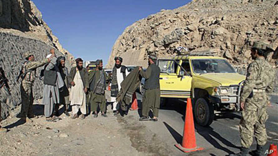 An Afghan policeman, left, searches men at a check point in Kandahar,  12 Dec, 2010