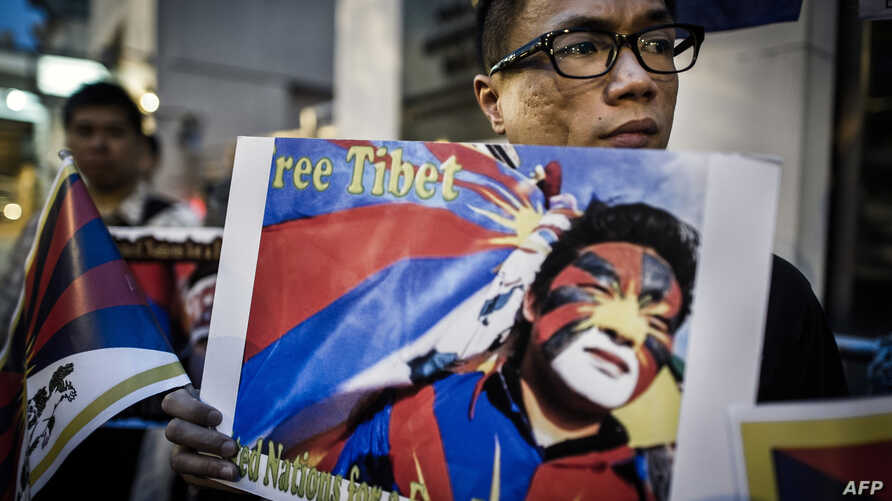 Rights group activists stage a protest to raise awareness on the human rights situation in Tibet and the closure of the territory to foreign visitors, outside the Chinese liaison office in Hong Kong on June 20, 2012.