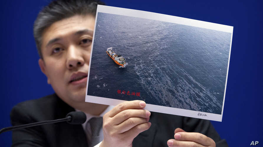 Huo Chuanlin, deputy director of the Department of Ecological and Environment Protection of China's State Oceanic Administration, holds a photo showing a rescue ship and an oil slick during a press conference about the Iranian oil tanker Sanchi, whic