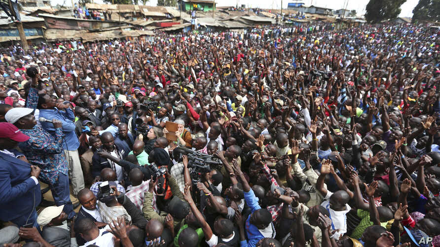 Kenyan opposition leader Raila Odinga, far left, holds a microphone as he addresses supporters in the Kibera area of Nairobi, Kenya, Aug. 13, 2017. Odinga urged his supporters to skip work on Monday in a protest against the country's disputed electio