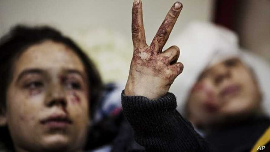 Hana, 12, flashes the victory sign next to her sister Eva, 13, as they recover from severe injuries after the Syrian Army shelled their house in Idlib, north Syria. (March 10, 2012 file photo)